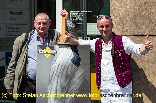 Stefan Caspari (Künstler) und Jens Krumpholz (PARKETTBÖRSE Pasing) vor einem Plakat des Künstlers