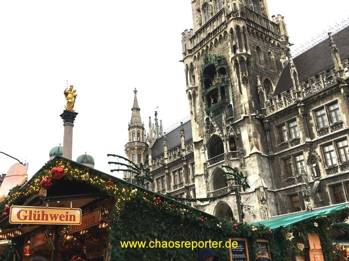 Über den Dächern des Marktes das Glockenspiel des neuen Rathauses München