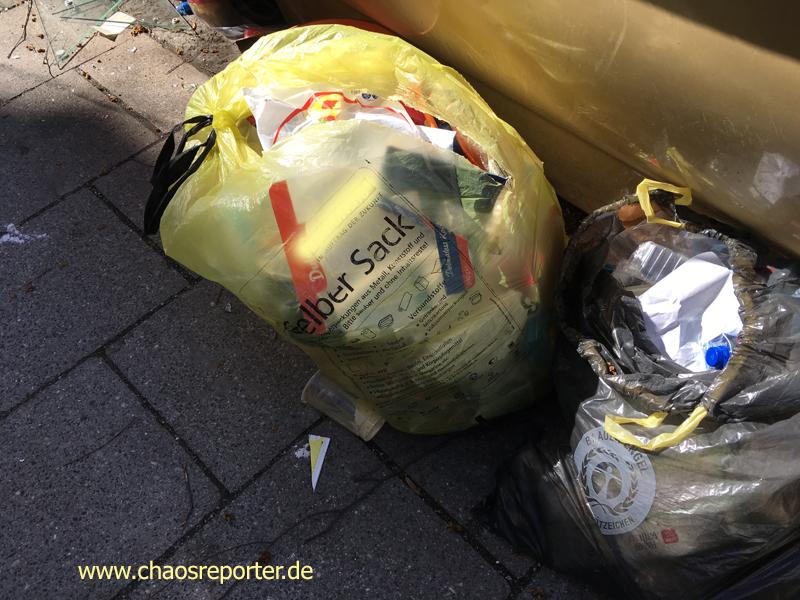 Sack einer benachbarten Gemeinde einfach vor Container geworfen. Flaschensammler reißen Tüten auf um nach Flaschen zu suchen.